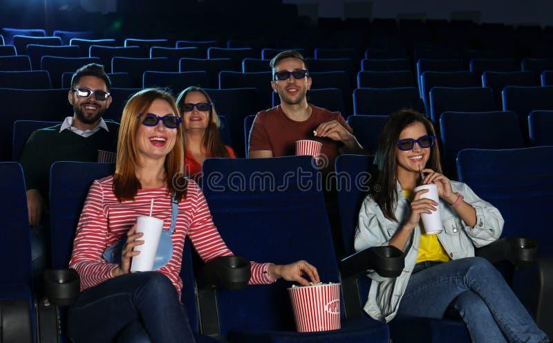 Молодые люди смотря кино в кино стоковое изображение