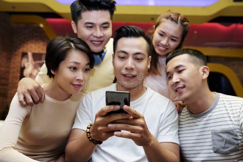 Молодые люди смотря смартфон друга стоковое изображение