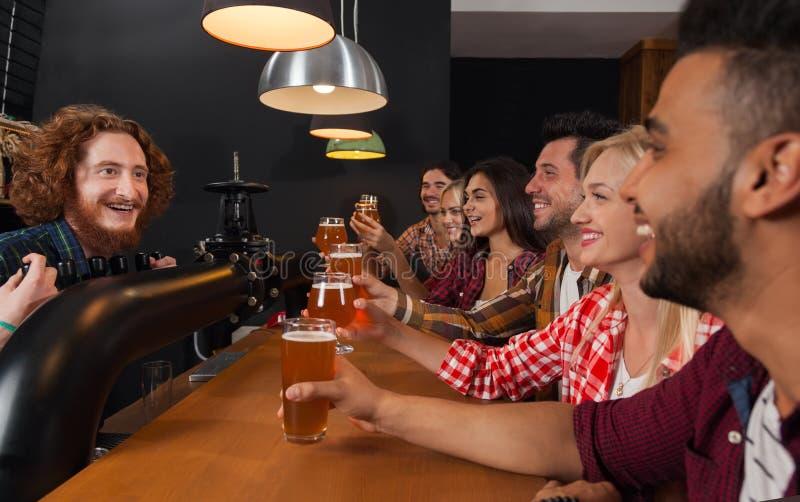 Молодые люди собирает в бар, друзей бармена сидя на пабе деревянной стойки, пиве питья стоковое изображение rf