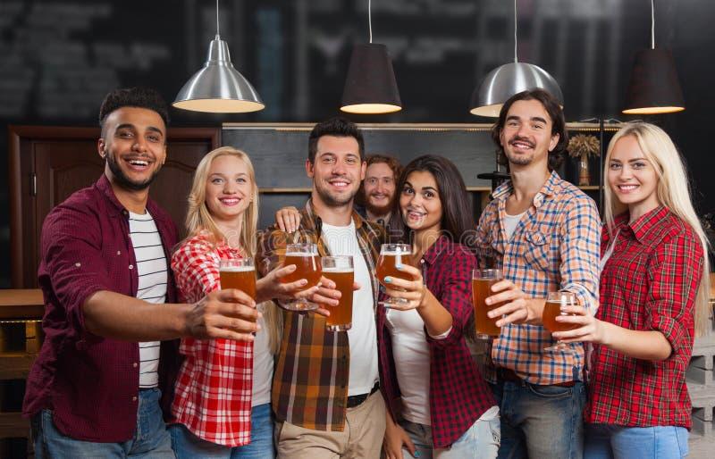 Молодые люди собирает в бар, счастливый усмехаясь паб друзей, приветственные восклицания пива питья стоковая фотография rf