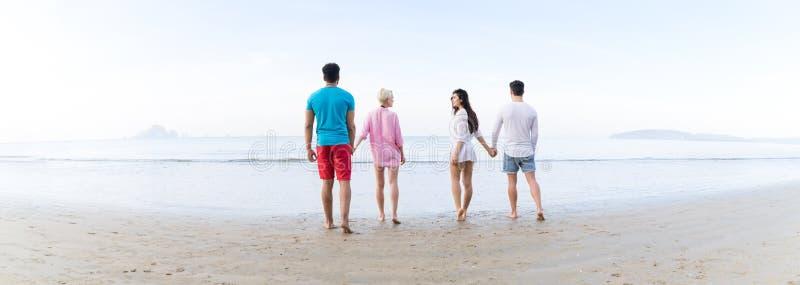 Молодые люди собирает на летние каникулы пляжа, вид сзади взморья друзей идя заднее стоковое фото