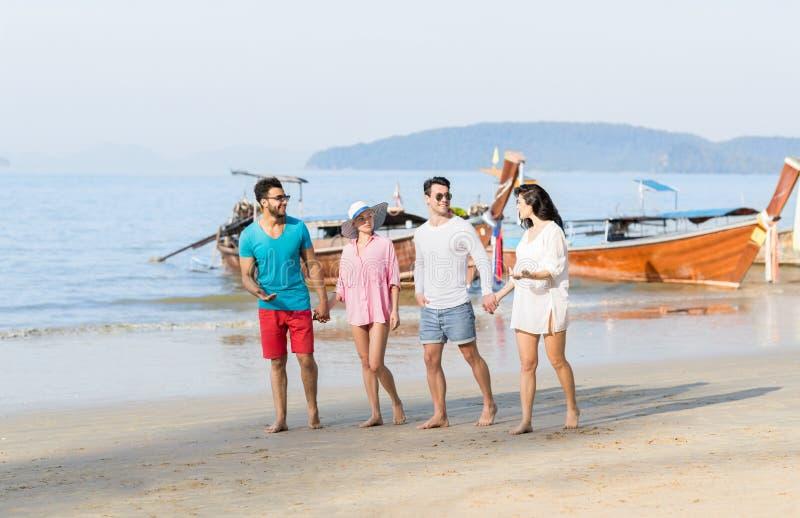 Молодые люди собирает на летние каникулы пляжа, счастливое усмехаясь взморье друзей идя стоковые фотографии rf