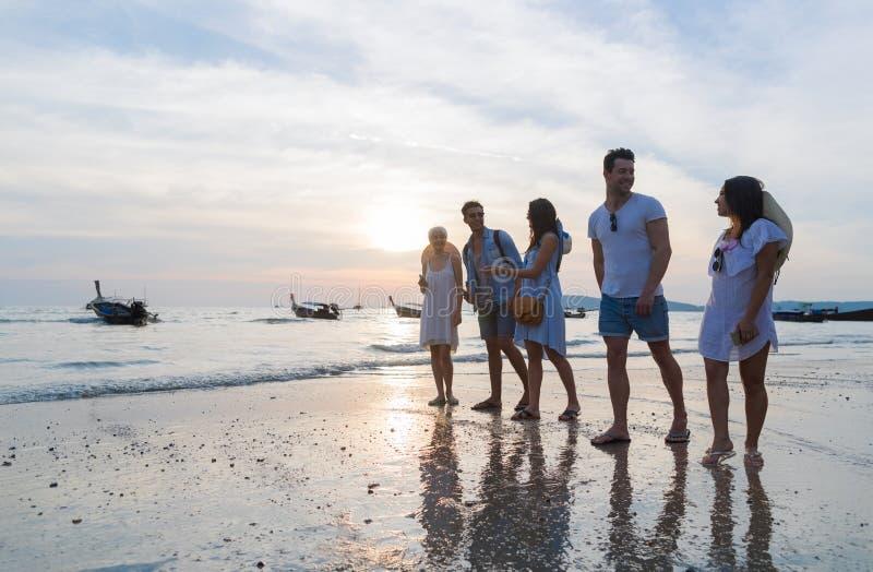Молодые люди собирает на пляж на летних каникулах захода солнца, взморье друзей идя стоковое фото rf