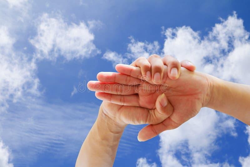 Молодые люди соединяя руки совместно в предпосылке голубого неба Единство и сыгранность концепции с космосом экземпляра стоковое фото