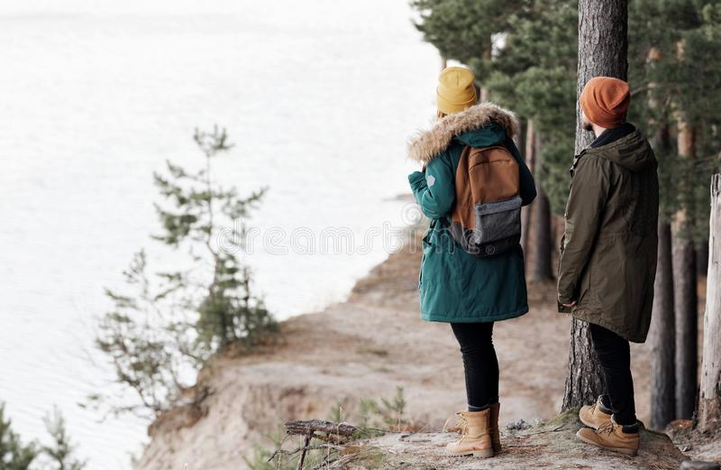Молодые люди стоя на скале соснового леса стоковая фотография