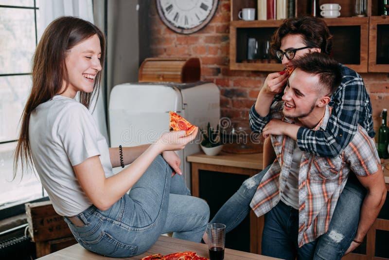 Молодые люди усмехаясь, ел пиццу и говорить стоковые изображения rf