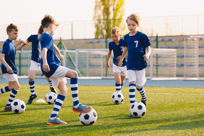 Молодые мальчики спортклуба на тренировке футбола футбола Дети улучшая навыки футбола на естественном тангаже травы дерновины стоковые изображения
