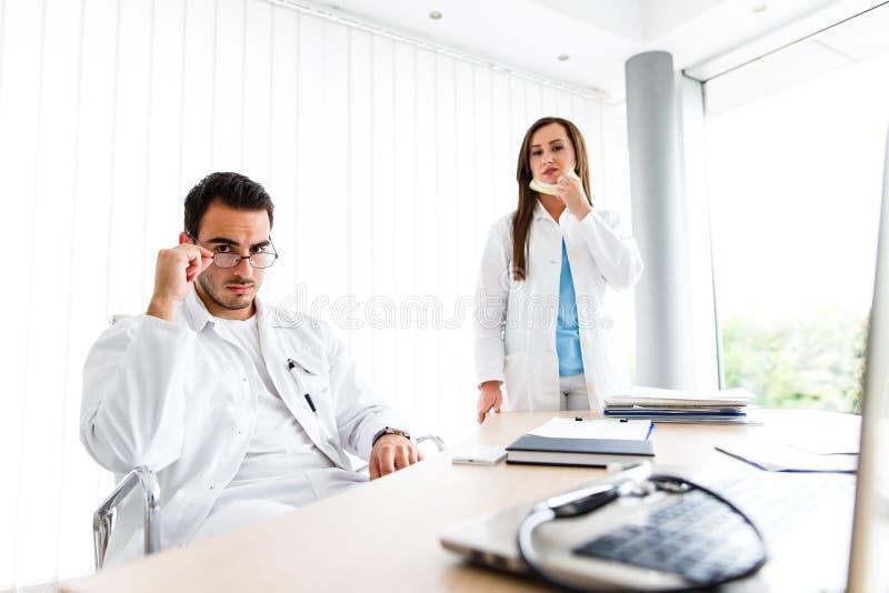 Молодые медицинские коллеги работая на компьтер-книжке стоковое изображение