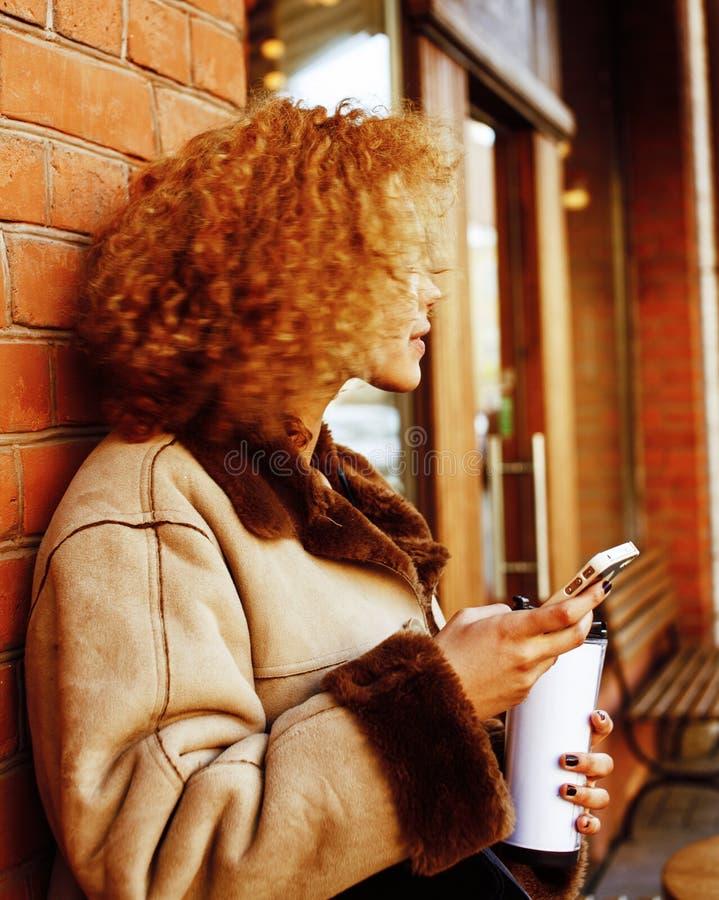 Молодые милые Афро-американские женщины выпивая кофе снаружи в c стоковое фото rf
