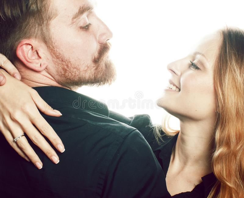 Молодые милые пары в huggings влюбленности изолированные на белом backgroun стоковая фотография