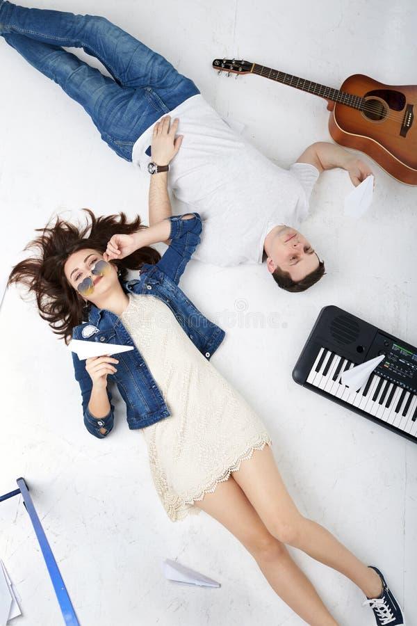Молодые музыканты, парень и девушка, ложь на поле в studi стоковое изображение rf