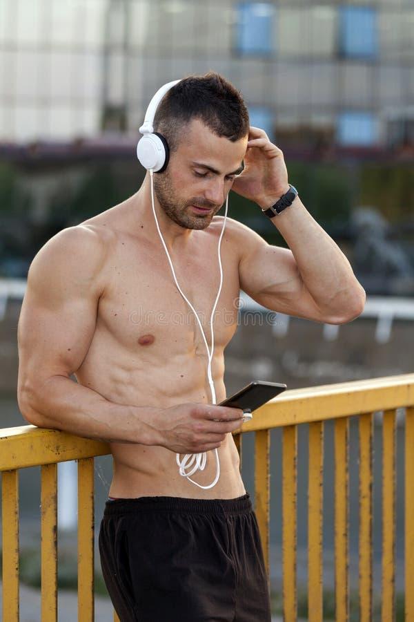 Молодые мышечные спортсмены отдыхают после тренировки пока слушающ к m стоковые изображения rf