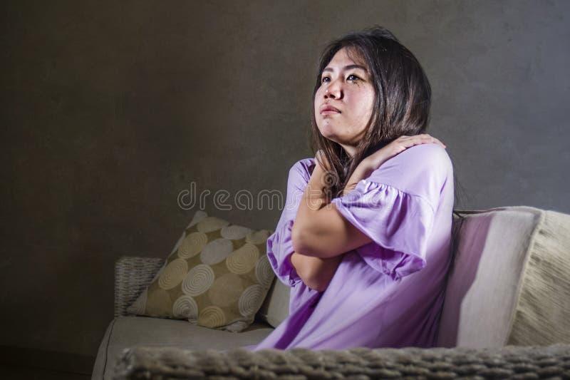 Молодые отчаянные унылой и подавленной азиатской корейской женщины плача одни и потревоженный в боли сидя дома страдание кресла с стоковые изображения rf