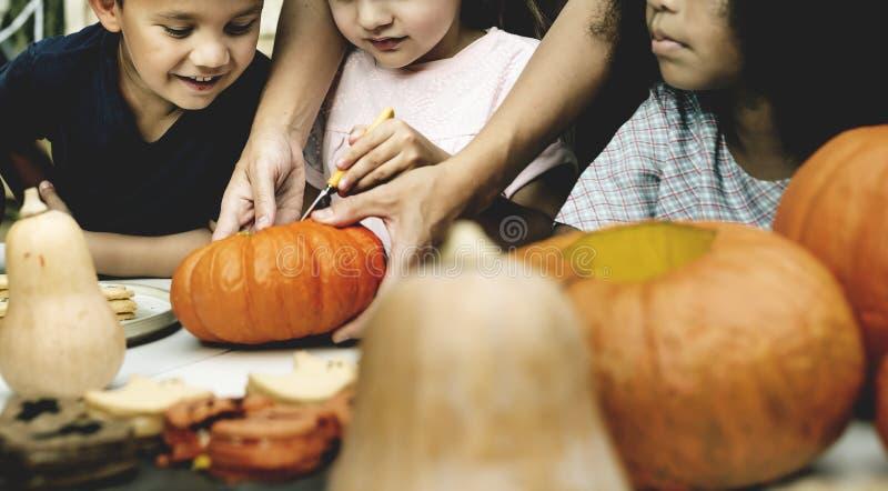 Молодые парни высекая ` хеллоуина Джека-o - фонарики стоковые фото