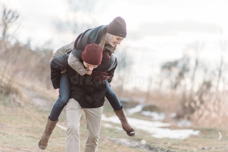 Молодые пары битника обнимая один другого в парке зимы стоковое изображение rf