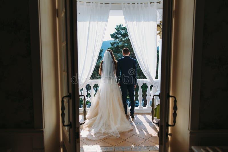 Молодые пары влюбленн в новобрачные стоя на белом балконе и держа руки, вид сзади Невеста в красивом стоковые изображения
