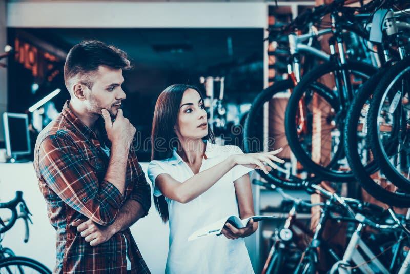 Молодые пары выбирают велосипед смотрят каталог в магазине стоковая фотография