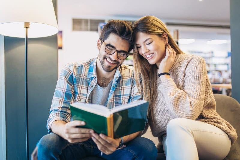 Молодые пары в библиотеке читая книгу совместно стоковые изображения