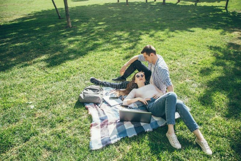 Молодые пары в влюбленности отдыхая на лужайке после школы на солнечный день стоковые изображения