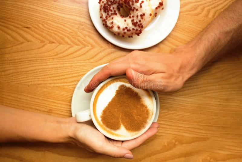 Молодые пары в влюбленности сидят в кафе, руках держа чашку кофе с сердцем искусства и 2 donuts на плите на предпосылке деревянно стоковое изображение rf