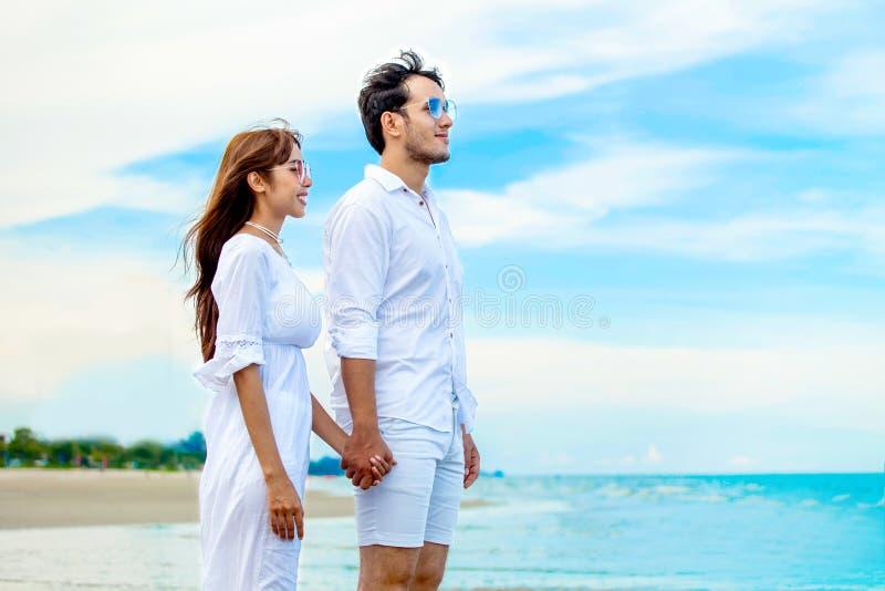 Молодые пары в любов смотря будущее и держа пляж руки совместно на море на голубом небе счастливая усмехаясь молодая свадьба с стоковое изображение