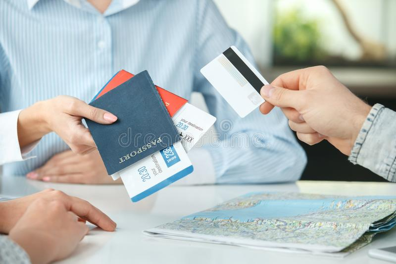 Молодые пары в связи агенства путешествия при агент по путешествиям путешествуя конец-вверх оплаты кредитной карточки концепции стоковое фото rf