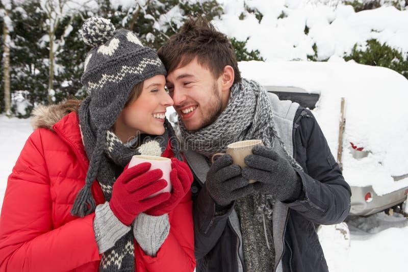 Молодые пары в снежке с автомобилем стоковое изображение