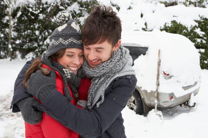 Молодые пары в снежке с автомобилем стоковое фото rf