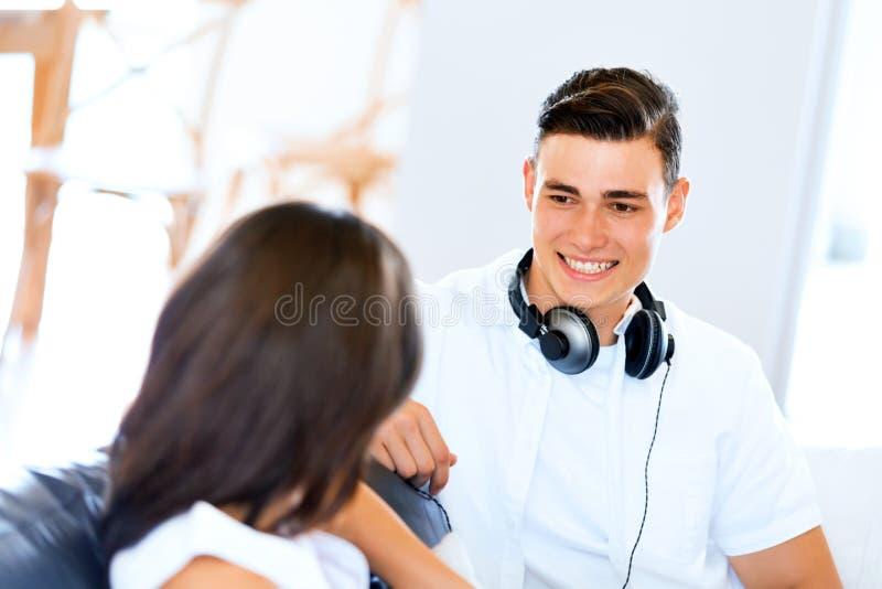 Молодые пары говоря пока сидящ дома стоковая фотография