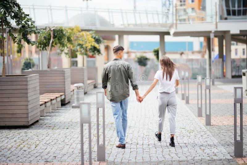 Молодые пары датировка в влюбленности идя в город Бизнесмены или коллеги офиса flirting после работы держа руки на улице стоковая фотография