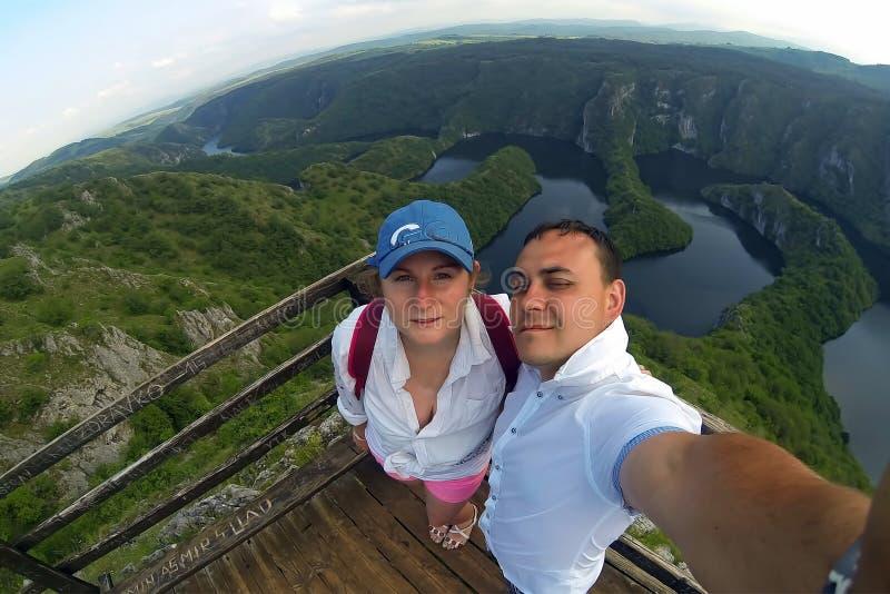 Молодые пары делая фото selfie на точке зрения Верхняя часть холма и панорамы каньона Uvac в Сербии стоковое фото rf