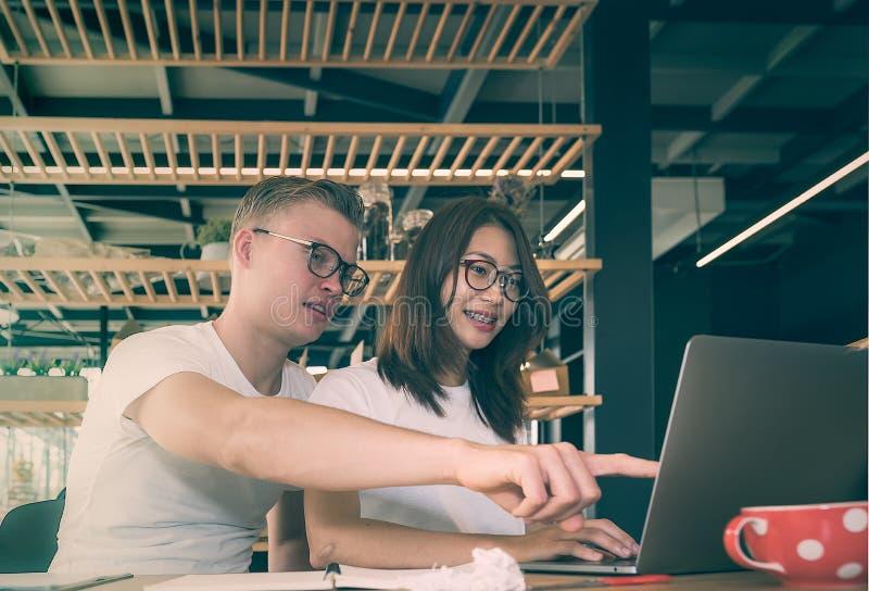 Молодые пары дела работая с компьтер-книжкой совместно стоковые изображения