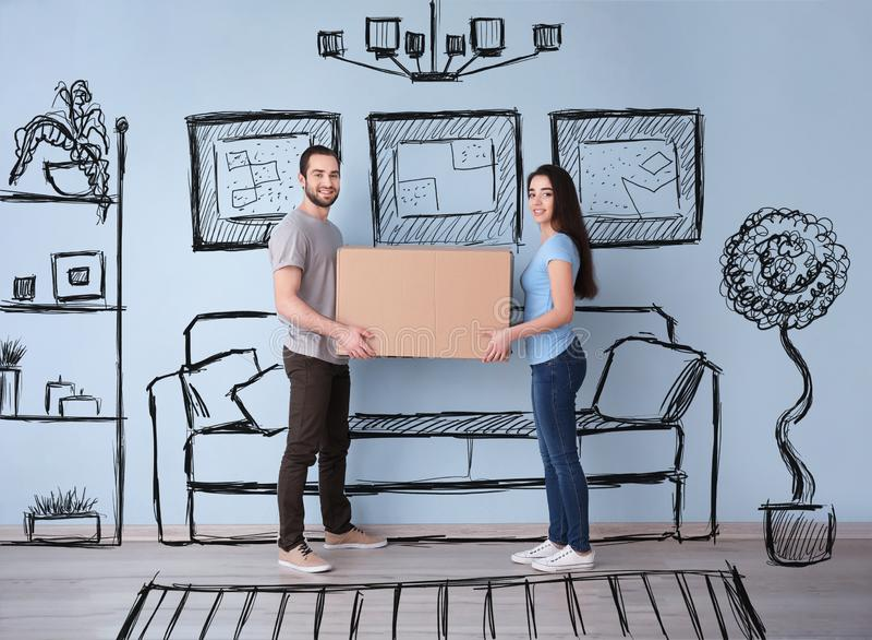 Молодые пары держа коробку внутри помещения и представляя интерьер нового дома Двигая день стоковые фотографии rf