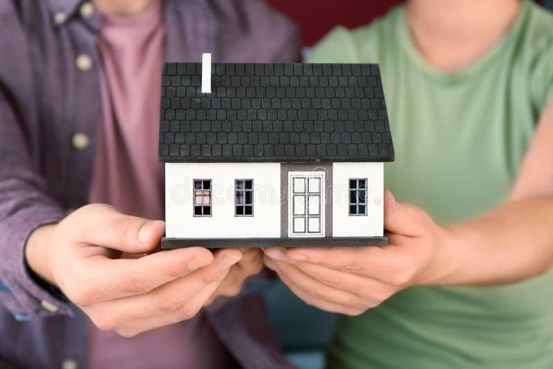 Молодые пары держа модель дома, крупный план Концепция ипотеки стоковое фото rf