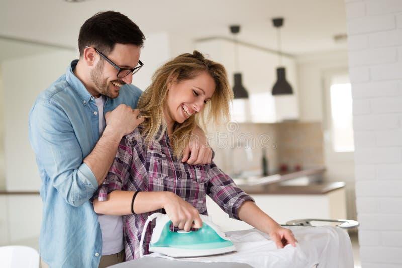 Молодые пары дома делая работы по дому и утюжить hosehold стоковая фотография