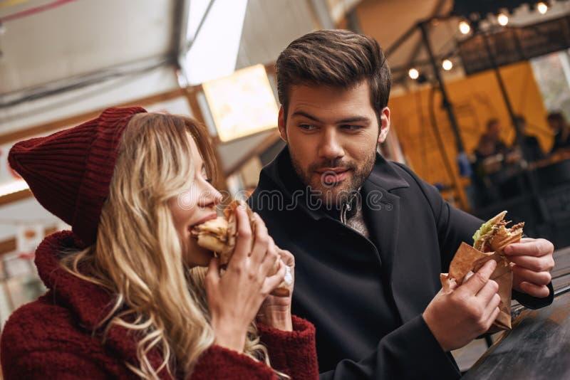 Молодые пары едят вне Удержание сэндвичей на продовольственном рынке улицы стоковое изображение rf