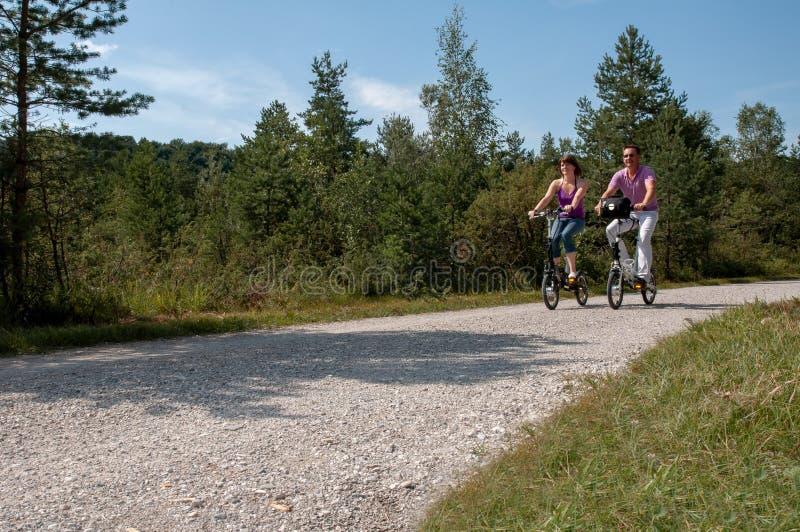 Молодые пары задействуя с современными небольшими e-велосипедами стоковые фото