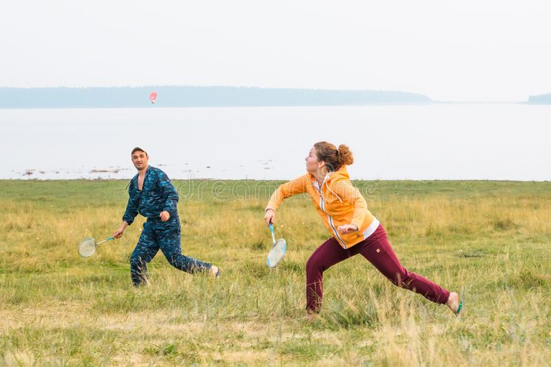Молодые пары играют бадминтон на озере Девушка бежит и подготавливает побить с shuttlecock с ракеткой стоковые фото