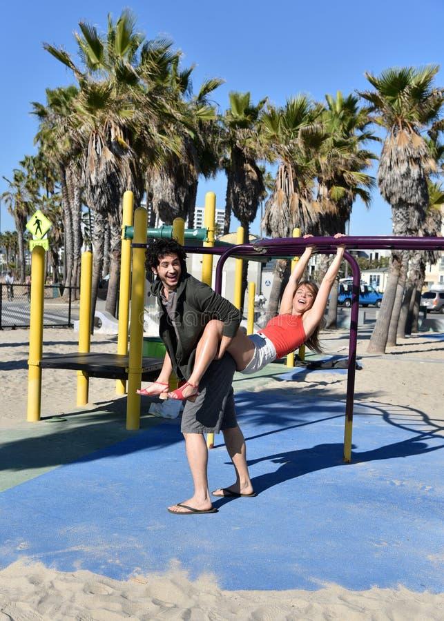 Молодые пары играя в спортивной площадке стоковые фото