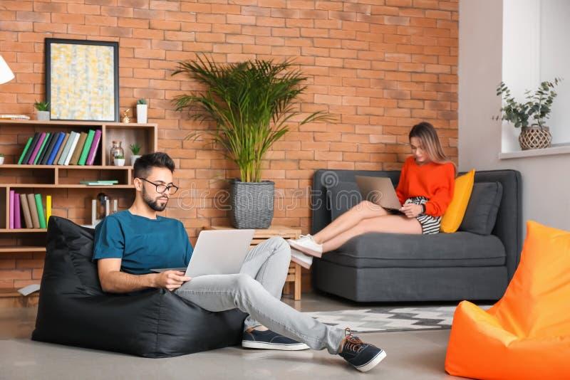 Молодые пары изучая с ноутбуками дома стоковые изображения