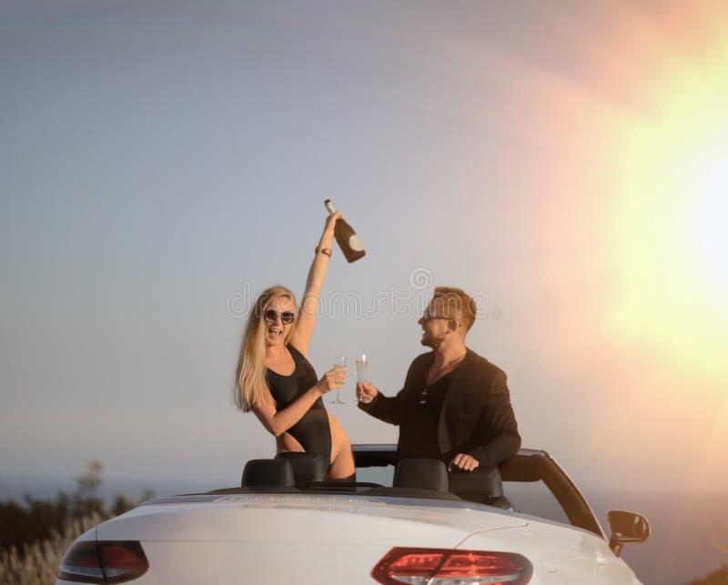 Молодые пары имеют шампанское партии праздника выпивая на приветственных восклицаниях пляжа стоковое изображение