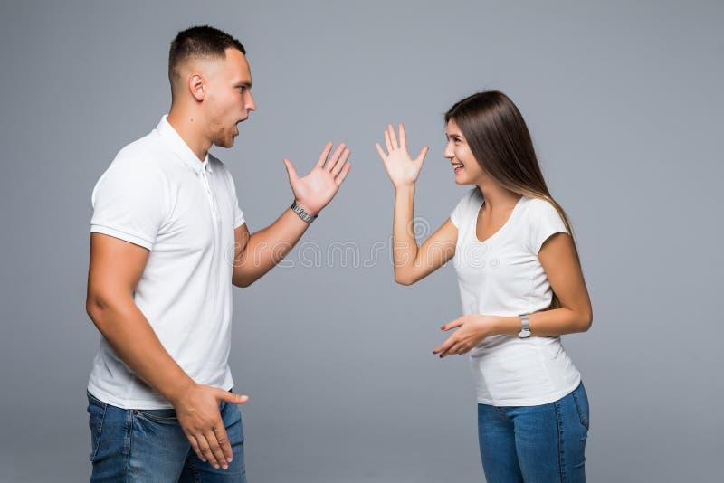 Молодые пары имея аргумент на серой предпосылке Проблемы отношения стоковая фотография