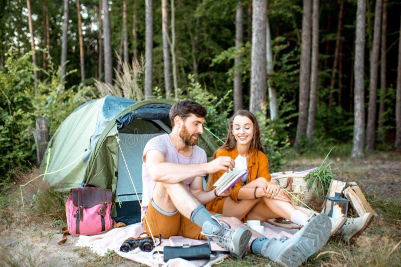 Молодые пары имея располагаться лагерем в лесе стоковые изображения rf