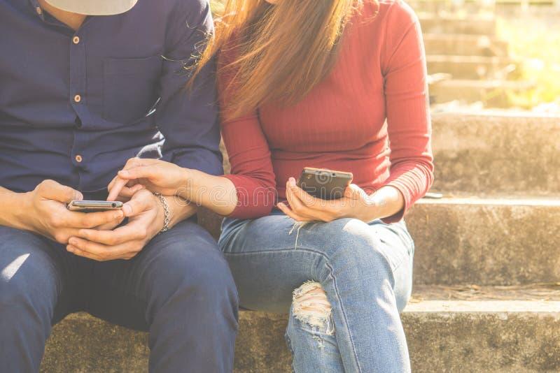 Молодые пары используя их smartphones сидят в парке, который транспортирует концепции средств массовой информации social технолог