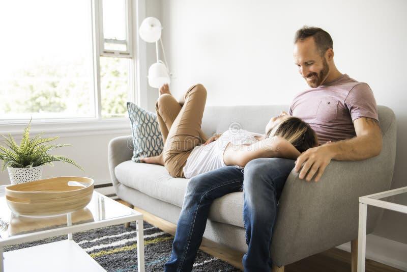Молодые пары кладя на софу ослабляя дома стоковые фотографии rf