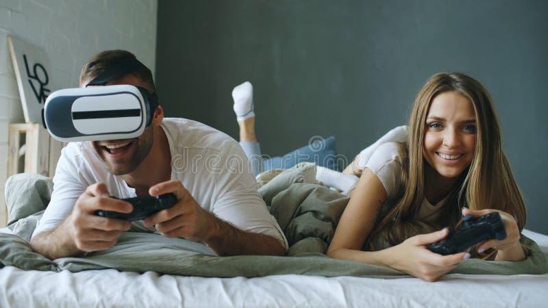 Молодые пары лежа в кровати играют видеоигры с регулятором и шлемофоном VR стоковая фотография rf