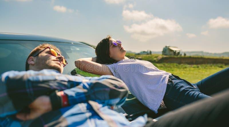 Молодые пары лежа на лобовом стекле стоковые изображения