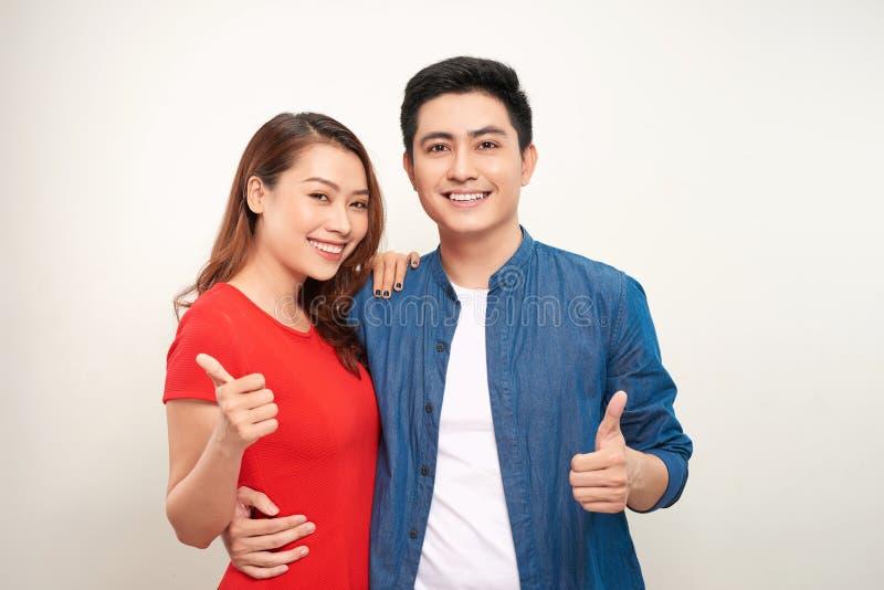 Молодые пары над изолированной предпосылкой усмехаясь со счастливой стороной смотря и указывая на сторону с большим пальцем руки  стоковая фотография rf