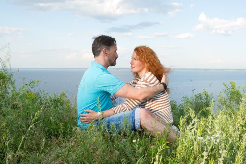 Молодые пары на пикнике на речном береге под облаками в небе Пары обнимая и смотря один другого стоковое изображение rf