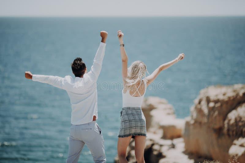 Молодые пары на пляже океана наслаждаясь их летними каникулами, оружиями протянули вне к солнцу как символ свободы Лето стоковая фотография